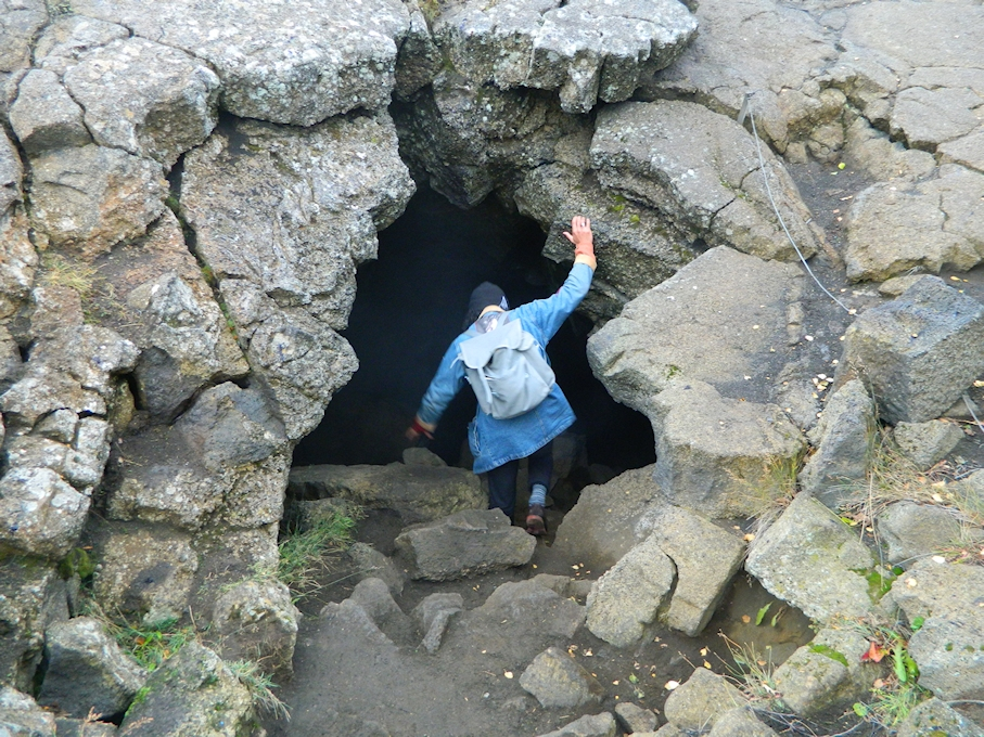 a figure entering a mysterious cave
